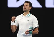 Serbia's Novak Djokovic celebrates after defeating Canada's Milos Raonic during their fourth round match at the Australian Open tennis championship in Melbourne, Australia, Sunday, Feb. 14, 2021.(AP Photo/Hamish Blair)