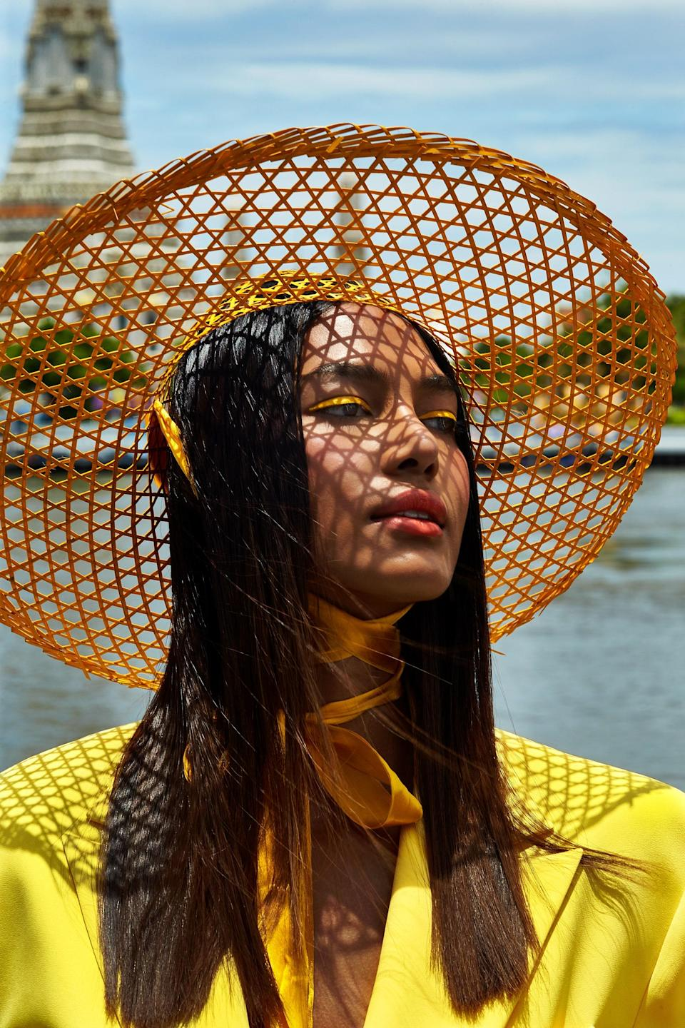 """""""I was rejected at castings a lot, not only for my skin tone, but because I am trans. Many trans models tell me that my winning [The Face Thailand] has opened doors for them, but it has been very tough,"""" says Candy Kulchaya. Her yellow liner was """"inspired by the marigold flower that we use here for garlands,"""" says Barose. He used NYX Professional Makeup EpicWear Liner Stick in Cosmic Yellow, and then, to add more intensity, layered matching yellow powder eye shadow over it using a dampened liner brush. Irada top. Stylist's own hat."""