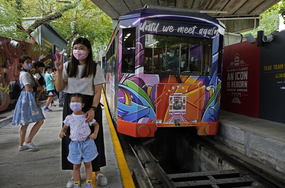 Passengers pose next to a Peak Tram on June 16, 2021. Hong Kong's Peak Tram is a fixture in the memories of many residents and tourists, ferrying passengers up Victoria Peak for a bird's eye view of the city's many skyscrapers. (AP Photo/Vincent Yu)