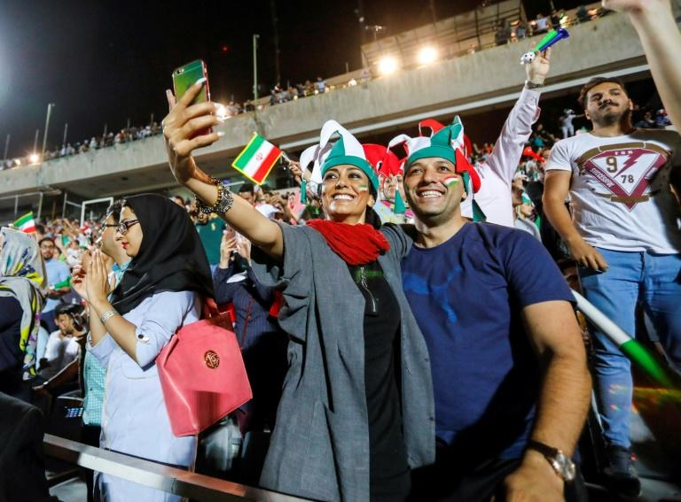 """An Iranian couple pose for a """"selfie"""" while cheering for their national fooball team during a screening of a Russia 2018 World Cup Group B football match between Iran and Spain at Azadi stadium in Tehran on June 20, 2018"""