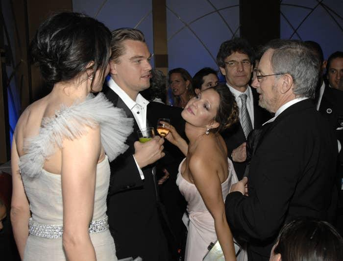 Drew Barrymore stands near Leonardo DiCaprio while holding a wine glass and leaning in towards Cameron Diaz, with Steven Spielberg behind her