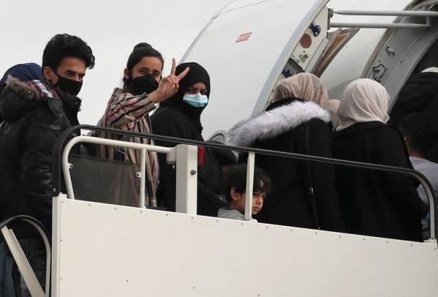 Refugees and migrants board their flight to Britain at the Athens International Airport