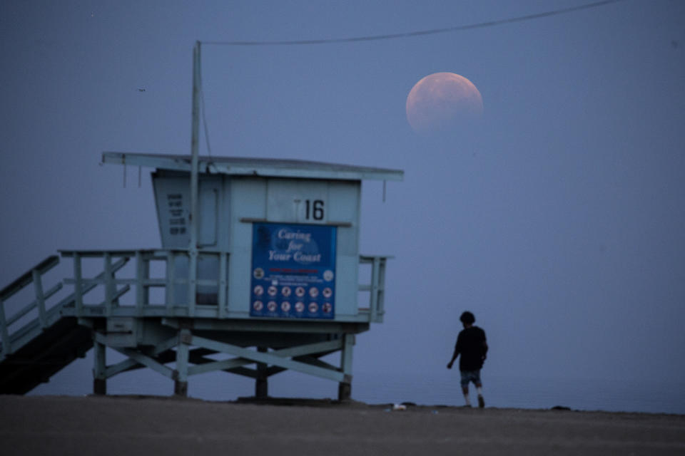 <p>A woman watches as the full-moon sets over Santa Monica Beach in Santa Monica, Calif., Wednesday, May 26, 2021. The first total lunar eclipse in more than two years is coinciding with a supermoon for quite a cosmic show. (AP Photo/Ringo H.W. Chiu)</p>