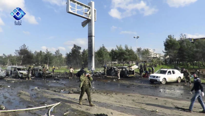 This frame grab from video provided by the Thiqa News Agency, shows rebel gunmen gathered at the site of a blast that damaged several buses and vans at the Rashideen area, a rebel-controlled district outside Aleppo city, Syria, Saturday, April. 15, 2017. Syrian TV said at least 39 people were killed Saturday in an explosion that hit near buses carrying evacuees from two towns besieged by rebels nearby. (Thiqa News via AP)