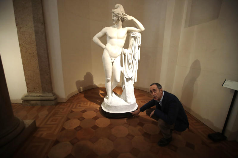 Giulio Manieri Elia, Director of the Accademia Gallery points the level reached by the water at the base of plaster cast sculpture 'Paride' by Antonio Canova, at the Accademia gallery, during an interview with The Associated Press in Venice, Saturday, Nov. 16, 2019. As high tidal waters returned to Venice on Saturday, four days after the city experienced its worst flooding in 50 years, young Venetians are responding to the worst flood in their lifetimes by volunteering to help salvage manuscripts, clear out waterlogged books and lend a hand where needed throughout the stricken city. (AP Photo/Luca Bruno)