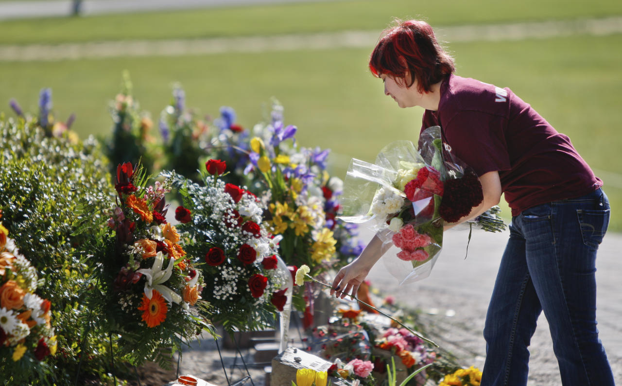 A visitor to the April 16 memorial lays flowers in remembrance on the Virginia Tech campus, Monday, April 16 2012, in Blacksburg, Va. Each anniversary since the April 2007, massacre on the Virginia Tech campus, classes have been suspended for the day in memory of the 32 students and faculty killed in the rampage by a lone gunman who then killed himself. On Monday, the fifth anniversary of the deadliest mass shooting in modern U.S. history, the 28,000 students on campus will head to class to honor the 32. (AP Photo/The Roanoke Times, Daniel Lin)
