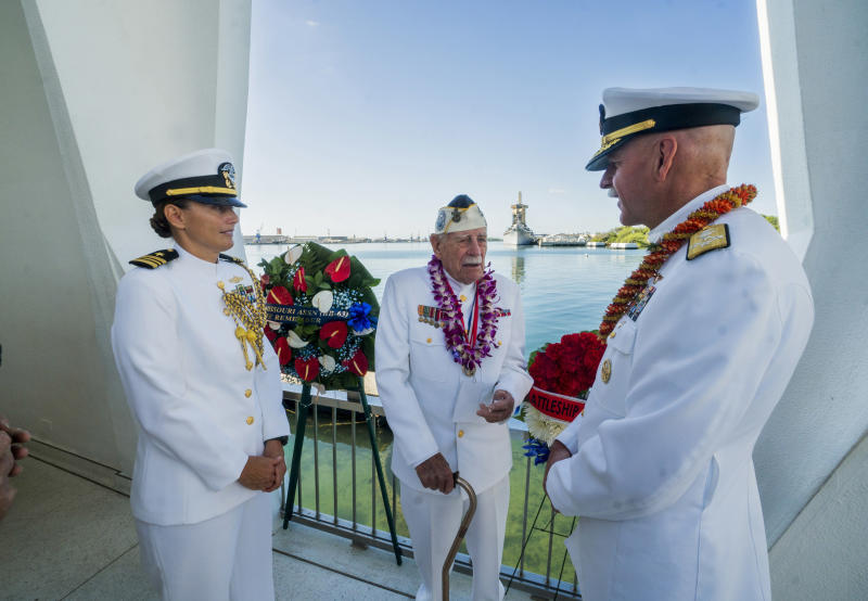 Lt. Commander Colleen Moore, left, and Adm. Scott Swift, right, talk with Pearl Harbor survivor Delton Walling, center, during the National Pearl Harbor Remembrance Day ceremony at the Arizona Memorial Thursday, Dec. 7, 2017, in Honolulu, Hawaii. The USS Missouri is in the background. (Dennis Oda /The Star-Advertiser via AP, Pool)