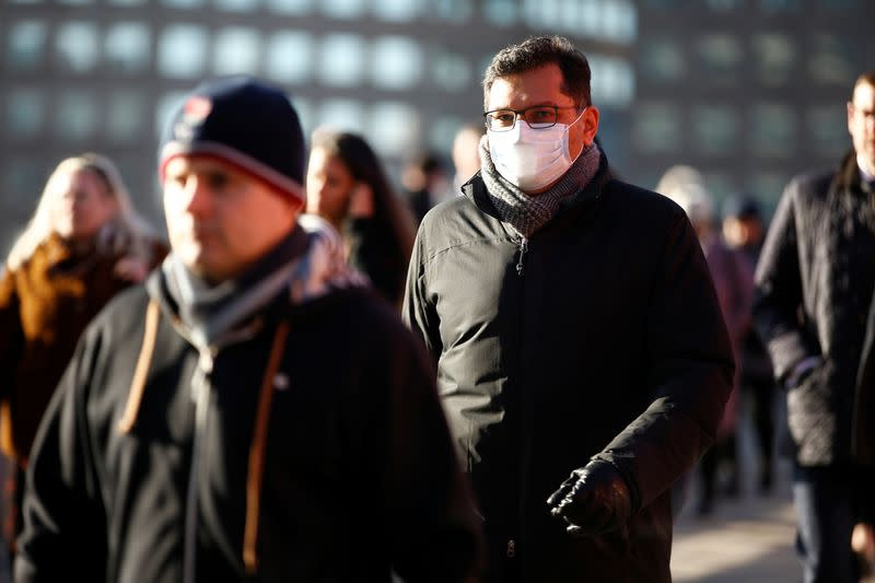 People, some wearing protective face masks, walk over London Bridge, as the number of coronavirus cases worldwide continues to grow, in London