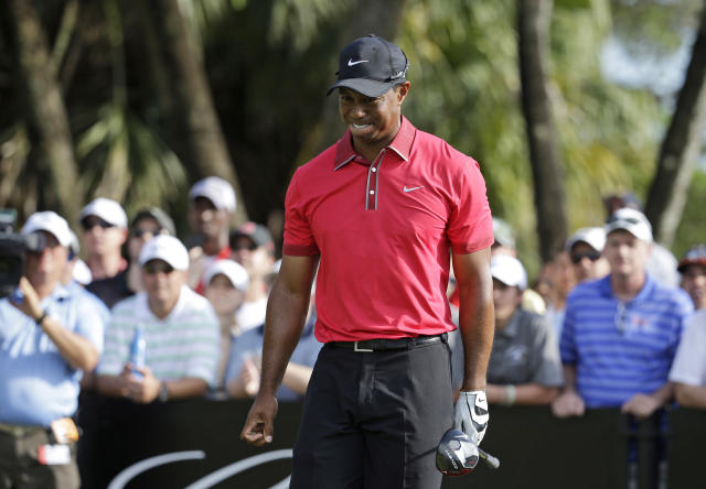 FILE - In this March 9, 2014 file photo, Tiger Woods grimaces after teeing off on the 12th hole during the final round of the Cadillac Championship golf tournament in Doral, Fla. Woods will miss the Masters for the first time in his career after having surgery on his back. Woods said on his website that he had surgery Monday, March 31, 2014, in Utah for a pinched nerve that had been hurting him for several months. (AP Photo/Lynne Sladky, File)