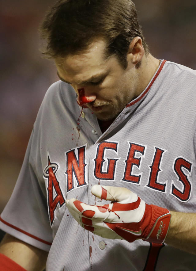 Blood pours out of Los Angeles Angels Collin Cowgill after he foul tipped a bunt into the bridge of his nose during the eighth inning of a baseball against the Texas Rangers in Arlington, Texas, Saturday, July 12, 2014. The Angels won 5-2. (AP Photo/LM Otero)