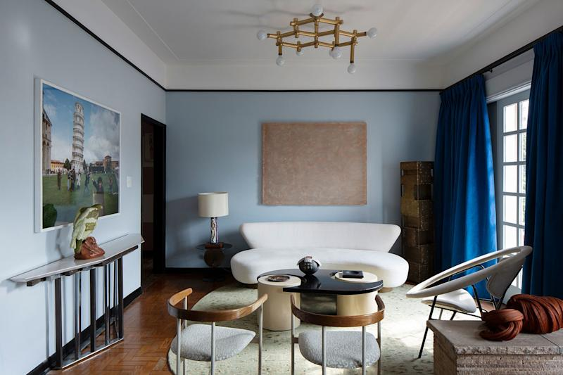"Juliana chose a grayish blue for the walls and made the ceiling white to keep it bright and fresh. ""I love the combination of the artwork behind the sofa (by Dudi Maia Rosa) and the other colors of the room."" Juliana designed the sofa with her ex-partner Matheus Barreto. The ceiling lamp is by Robert Haussmann and the coffee table is by Terry Della Stufa."