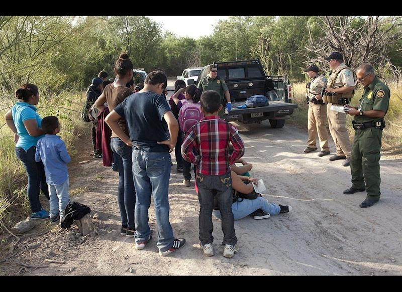 U.S. Customs and Border Protection officers gather information from unaccompanied children and others after they crossed the border into the United States. (Barry Bahler — Customs and Border Protection)