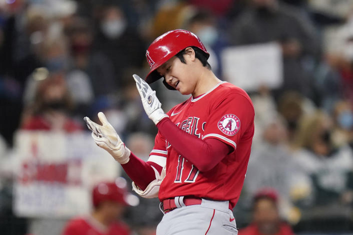 Los Angeles Angels' Shohei Ohtani claps his hands together as he crosses home on his solo home run against the Seattle Mariners in the first inning of a baseball game Sunday, Oct. 3, 2021, in Seattle. (AP Photo/Elaine Thompson)