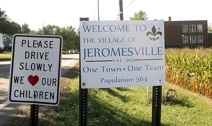 Jeromesville signs mark the village limits on the north on Ohio Route 89. In the background is a school built in 1929.