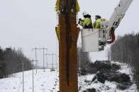 Workers connect a section of the first pole of Central Maine Power's controversial hydropower transmission corridor, Tuesday, Feb. 9, 2021, near The Forks, Maine. The pole was erected on an existing corridor that had been widened near Moxie Pond. (AP Photo/Robert F. Bukaty)