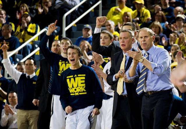Michigan coach John Beilein, right, and the Michigan bench cheer after a basket during the first half of an NCAA college basketball game against Minnesota at Crisler Center in Ann Arbor, Mich., Saturday, March 1, 2014. Michigan won 66-56. (AP Photo/Tony Ding)