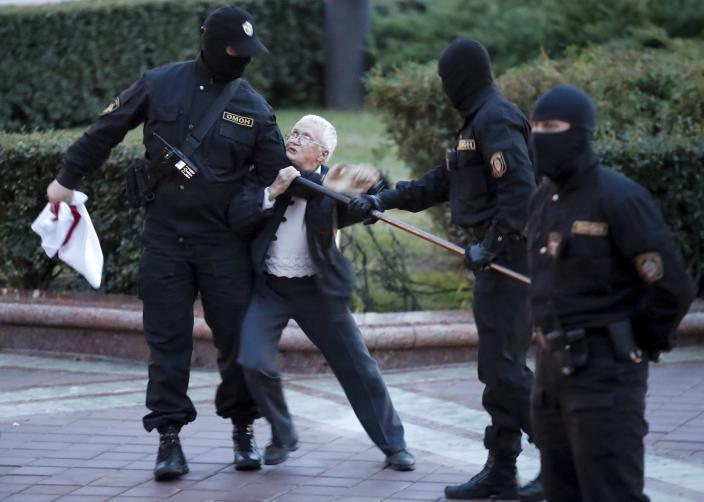 Opposition activist Nina Baginskaya, 73, center, struggles with police during a Belarusian opposition supporters rally at Independence Square in Minsk, Belarus, Wednesday, Aug. 26, 2020. Police in Belarus have dispersed protesters who gathered on the capital's central square, detaining dozens. The crackdown in Independence Square on Wednesday comes on the 18th straight day of protests pushing for the resignation of Belarus' authoritarian President Alexander Lukashenko. (AP Photo/Dmitri Lovetsky)