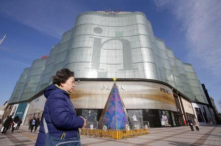A woman walks past an Intime Lotte Department Store in downtown Beijing, China January 10, 2017. REUTERS/Jason Lee