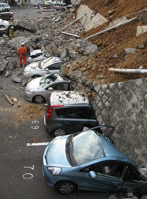 Vehicles are crushed by a collapsed wall at a carpark in Mito city in Ibaraki prefecture on March 11, 2011 after a massive earthquake rocked Japan. massive 8.9-magnitude earthquake hit Japan on March 11, unleashing a monster 10-metre high tsunami that sent ships crashing into the shore and carried cars through the streets of coastal towns. AFP PHOTO / JIJI PRESS