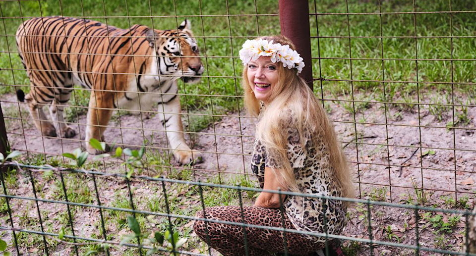Carole Baskin wearing a ring of flowers around her head and posing with a tiger.