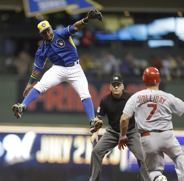 Milwaukee Brewers' Jean Segura leaps but can't catch a throw on a double by St. Louis Cardinals Matt Holliday (7) during the fourth inning of a baseball game Friday, July 11, 2014, in Milwaukee. (AP Photo/Jeffrey Phelps)