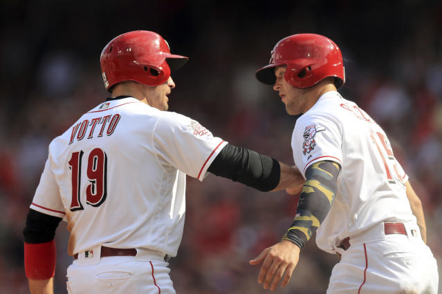 Cincinnati Reds' Joey Votto (19) celebrates after scoring a run with Nick Senzel (15), after a two-run single by Yasiel Puig (66) in the third inning of a baseball game against the Los Angeles Dodgers, Saturday, May 18, 2019, in Cincinnati. (AP Photo/Aaron Doster)