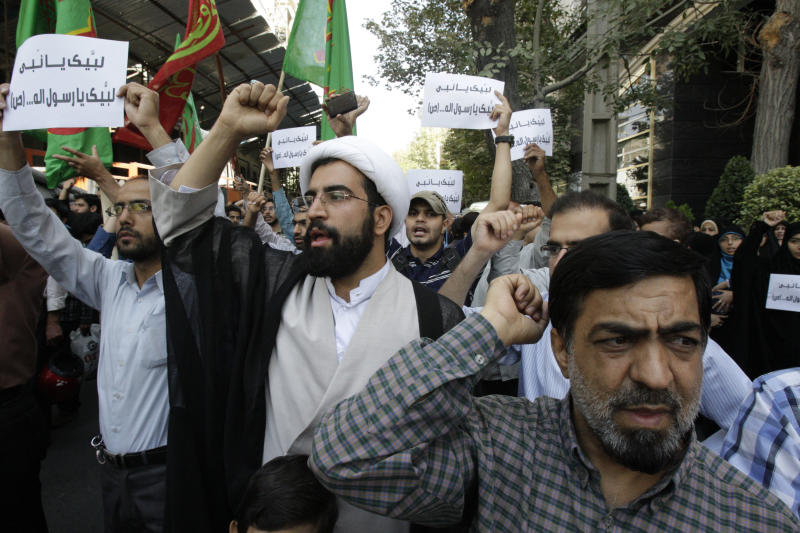 """Iranian protestors chant slogans during a demonstration against a film ridiculing Islam's Prophet Muhammad, in front of Swiss Embassy in Tehran, which represents US interests in Iran, Thursday, Sept. 13, 2012. The search for those behind the provocative anti-Muslim film led Wednesday to a California Coptic Christian convicted of financial crimes who acknowledged his role in managing and providing logistics for the production. Nakoula Basseley Nakoula, 55, told The Associated Press in an interview outside Los Angeles that he was manager for the company that produced """"Innocence of Muslims,"""" which mocked Muslims and the prophet Mohammed and was implicated in inflaming mobs that attacked U.S. missions in Egypt and Libya. (AP Photo/Vahid Salemi)"""