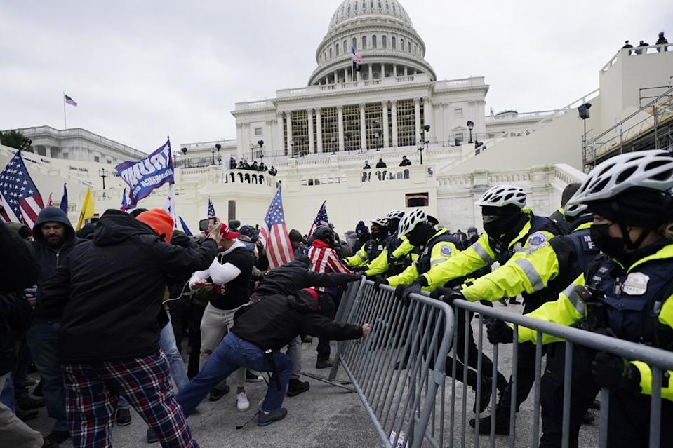 Police are seen trying to hold the protestors back from climbing over protective railing. Source: AP