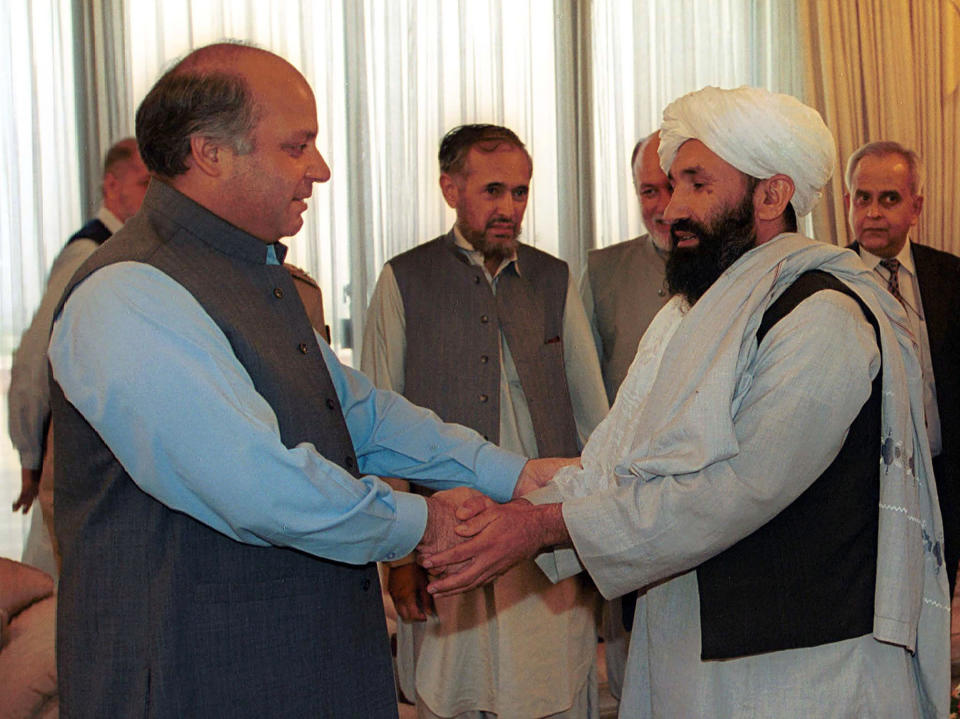 FILE - In this Aug. 25, 1999 file photo, Mullah Hasan Akhund, right, then Afghanistan's Foreign Minister is received by then Pakistan Prime Minister Nawaz Sharif, in Islamabad. The Taliban on Tuesday, Sept. 7, 2021, announced a caretaker Cabinet that paid homage to the old guard of the group, giving top posts to Taliban personalities who dominated the 20-year battle against the U.S.-led coalition and its Afghan government allies. Akhund who was named Interim Afghan Prime Minister on Tuesday, headed the Taliban government in Kabul during the last years of its rule. (AP Photo/B.K. Bangash, File)
