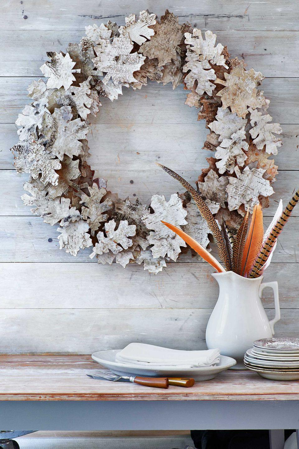 """<p>Birch bark is the key to these autumn """"leaves."""" You'll need 24 6 3/4""""W x 20 1/2""""L sheets of birch bark, a 20-inch-diameter foam wreath form, and 45 small wooden cubes to act as risers<em>. </em>First, print and cut out our <a href=""""http://clv.h-cdn.co/assets/cm/15/27/559438a2f0fa5_-_leaf-templates-1113.pdf"""" rel=""""nofollow noopener"""" target=""""_blank"""" data-ylk=""""slk:oak- and maple-leaf templates"""" class=""""link rapid-noclick-resp"""">oak- and maple-leaf templates</a>. Trace 75 assorted leaves onto the birch-bark sheets, and cut out. Varying the leaf type, hot-glue 30 leaves onto the wreath form. Then, hot-glue a wooden cube onto the back of each remaining leaf. Using our photo as a guide, hot-glue the cube-backed leaves atop the original leaves. </p>"""