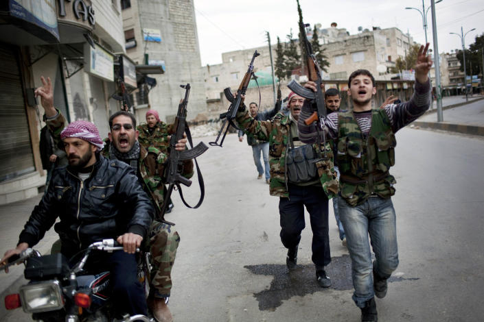 FILE - In this Sunday, March 11, 2012 file photo, Free Syrian Army fighters celebrate after hearing that their comrades destroyed a Syrian Army tank in Idlib, north Syria. In the previous days, troops had encircled Idlib, and tank shells pounded the city from dawn until evening. Rebels dashed through the streets, taking cover behind the corners of buildings as they clashed with the troops. Wounded fighters were piled into trucks bound for makeshift clinics. (AP Photo/Rodrigo Abd, File)
