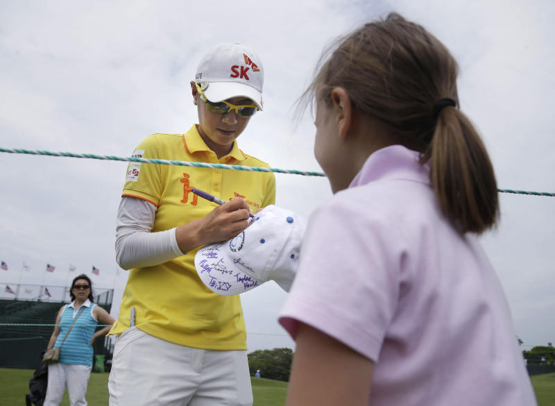 Na Yeon Choi , of South Korea, autographs a hat after a practice round for the U.S. Women's Open golf tournament at Sebonack Golf Club in Southampton, N.Y., Wednesday, June 26, 2013. (AP Photo/Seth Wenig)