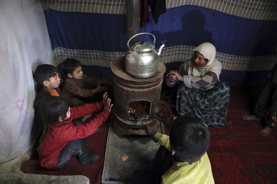 Internally displaced children sit around a stove to keep warm in a temporary shelter in the city of Kabul, Afghanistan, Wednesday, Dec. 30, 2020. Save the Children has warned that more than 300,000 Afghan children face freezing winter conditions that could lead to illness, in the worst cases death, without proper winter clothing and heating. (AP Photo/Rahmat Gul)