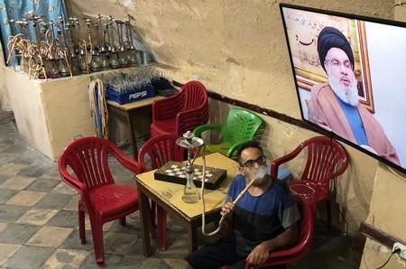 Man watches Lebanon's Hezbollah leader Sayyed Hassan Nasrallah on TV inside a coffee shop in Sidon