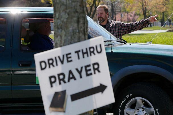 PHOTO: George DeCola, of Richmond, talks with someone who drove up for a prayer at a shopping center Thursday April 2, 2020, in Richmond, Va. DeCola, who is a worship leader at a Lutheran Church offers prayers for those wanting spiritual guidance. (Steve Helber/AP)