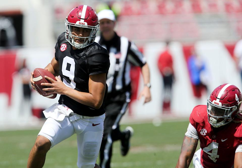 Quarterback Bryce Young (9) scrambles for a first down after moving away from Crimson linebacker Christopher Allen (4) during the Alabama A-Day game.