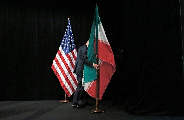 A worker removing the US and Iranian flags from the stage in Vienna on July 14, 2015 as foreign ministers came to a deal with iran on its nuclear programme (AFP Photo/Carlos Barria)