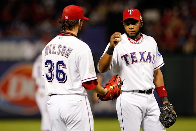 ARLINGTON, TX - OCTOBER 24: Elvis Andrus #1 of the Texas Rangers hands the ball to pitcher C.J. Wilson #36 during Game Five of the MLB World Series against the St. Louis Cardinals at Rangers Ballpark in Arlington on October 24, 2011 in Arlington, Texas. (Photo by Tom Pennington/Getty Images)