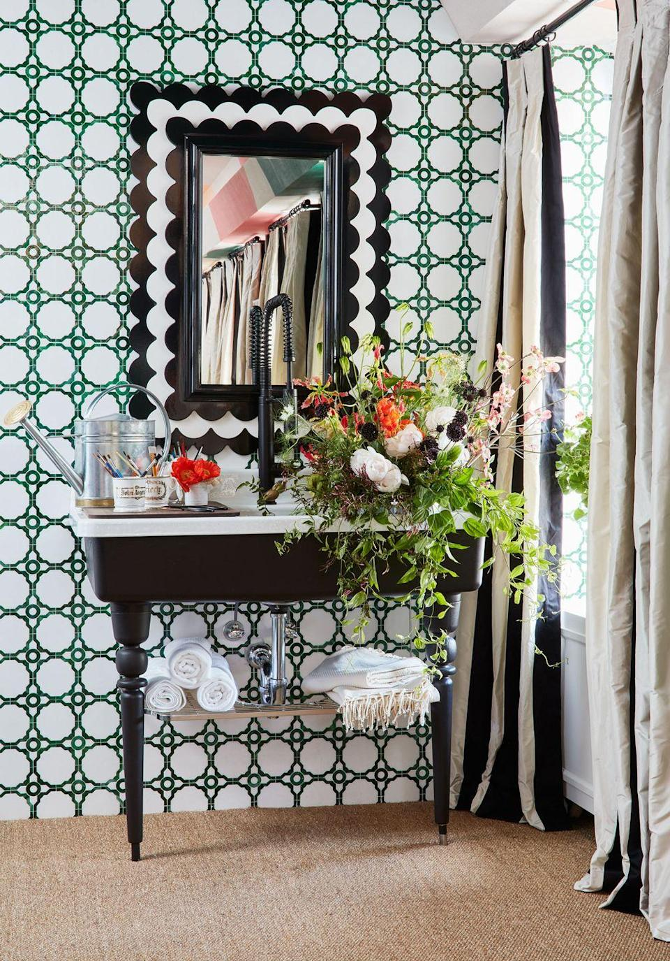 """<p>In her bathroom at the <a href=""""https://www.housebeautiful.com/design-inspiration/house-tours/g27334515/kips-bay-showhouse-2019/"""" rel=""""nofollow noopener"""" target=""""_blank"""" data-ylk=""""slk:Kips Bay show house,"""" class=""""link rapid-noclick-resp"""">Kips Bay show house,</a> designer Young Huh created an artful statement using her AKDO tiles in green and white plus a black-and-white mirror and sculptural black sink. Oh, and a bouquet of flowers never hurts! </p>"""