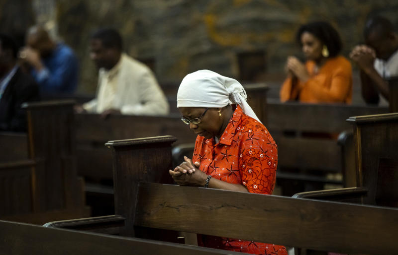 A woman prays during an early evening mass at the cathedral, which Pope Francis will visit later this week, in the capital Maputo, Mozambique Tuesday, Sept. 3, 2019. Pope Francis heads this week to the southern African nations of Mozambique, Madagascar and Mauritius, visiting some of the world's poorest countries in a region hard hit by some of his biggest concerns: conflict, corruption and climate change. (AP Photo/Ben Curtis)