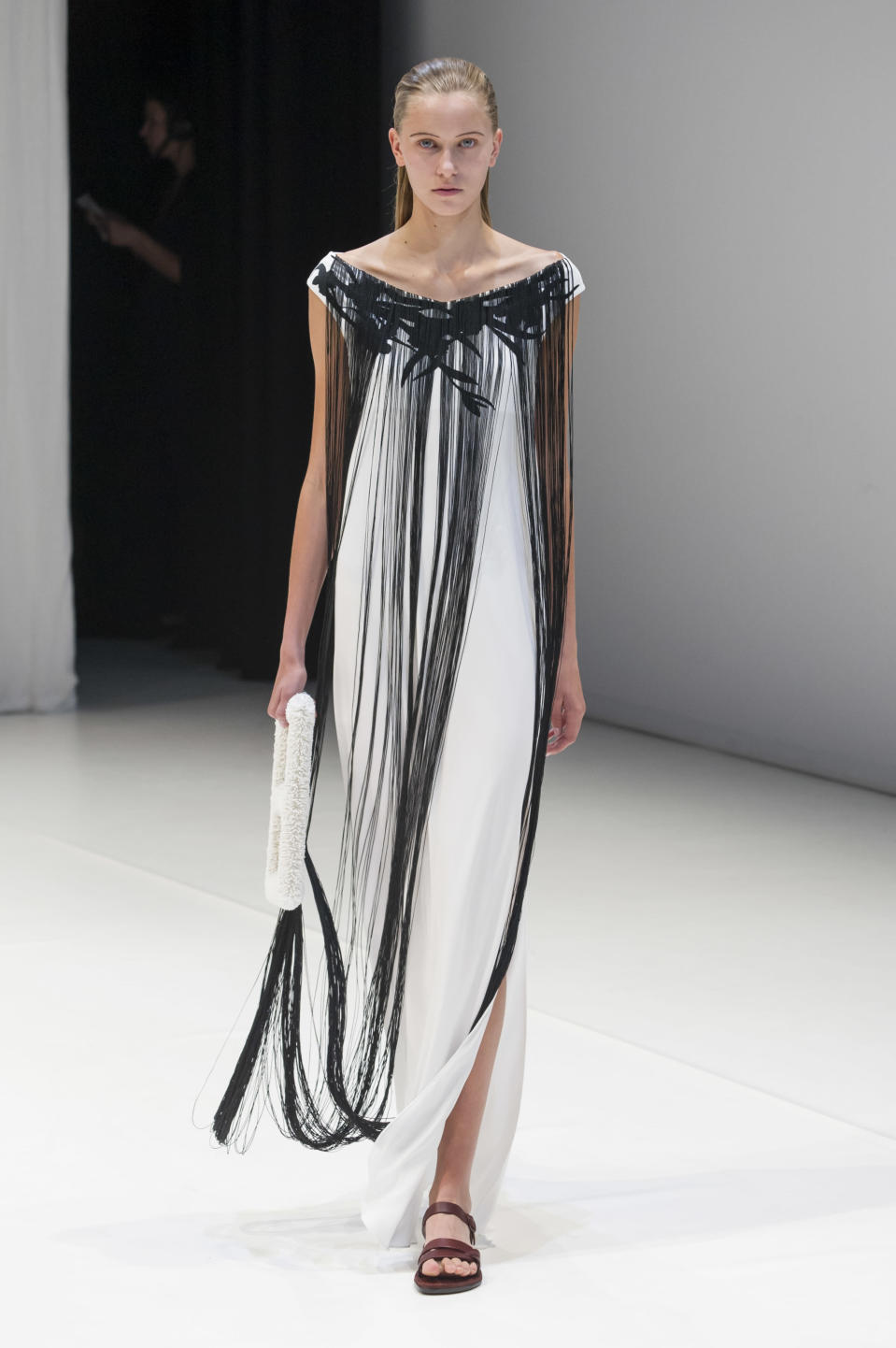 <p><i>White maxi dress with extra-long black-fringed collar from the SS18 Hussein Chalayan collection. (Photo: IMAXtree) </i></p>