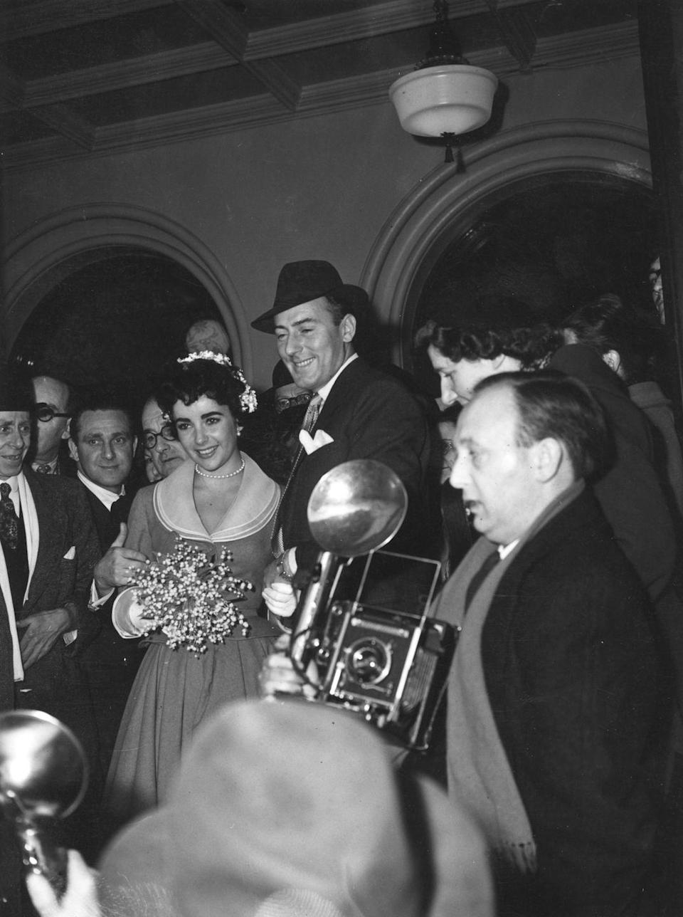 <p>Elizabeth Taylor's second wedding was less grand than her first. Wearing a simple belted dress and flowers in her chignon, Elizabeth and Michael Wilding got married at Caxton Hall in London. </p>