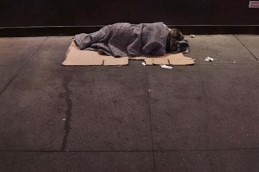 A homeless person sleeps on a Manhattan street on August 22, 2014 in New York