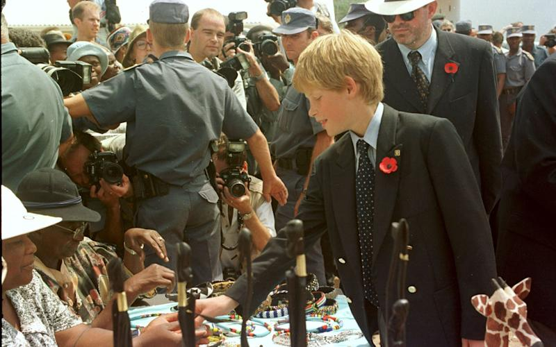 A young Prince Harry shopping for a Zulu bracelet during an overseas visit with his father in 2003