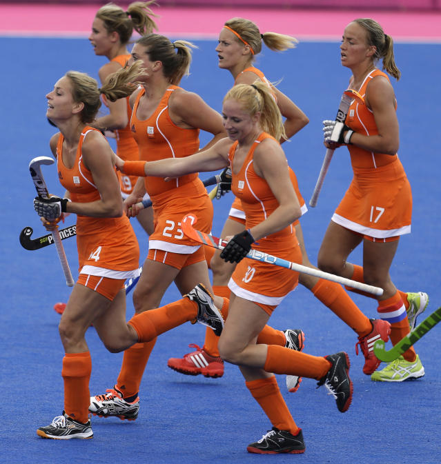 The Netherlands' Eva de Goede, left, is congratulated by teammates after scoring the first goal in the preliminaries match against Belgium at the 2012 Summer Olympics, Sunday, July 29, 2012, in London. (AP Photo/Bullit Marquez)