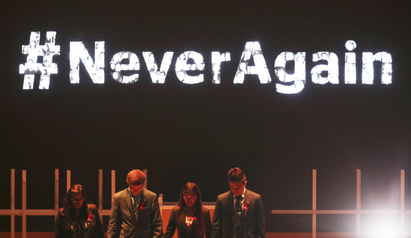 Moderator Vijita Patel, left, joins Parkland High School students Lewis Mizen, second left, Suzanna Barna, third left, and Kevin Trejos, right, in a moment of silence at the Global Education and Skills Forum in Dubai, United Arab Emirates, Saturday, March 17, 2018. Student survivors of a Florida high school shooting took their message calling for greater gun safety measures abroad for the first time on Saturday, sharing with educational professionals from around the world their frightening experience. (AP Photo/Jon Gambrell)