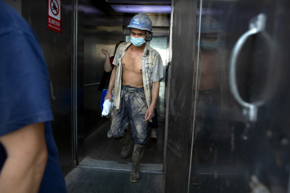 A construction worker wearing a face mask to protect against the coronavirus walks out of an elevator in Beijing, Wednesday, July 29, 2020. China reported more than 100 new cases of COVID-19 on Wednesday as the country continues to battle an outbreak in Xinjiang. (AP Photo/Mark Schiefelbein)