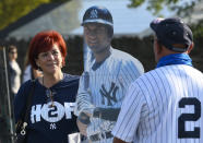 Noel Stazko of East Meadow, N.Y., left, stands in line with a cardboard cut out of Derek Jeter while talking with Peter Didier, of Charlotte, N.C., while attending the National Baseball Hall of Fame induction ceremony at the Clark Sports Center, Wednesday, Sept. 8, 2021, in Cooperstown, N.Y. (AP Photo/Hans Pennink)