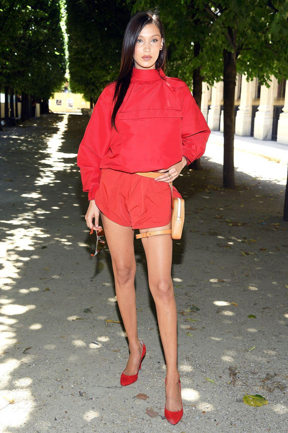 <p>In red romper suit, nude belt bag and red heels while attending the Louis Vuitton men's fashion show in Paris.</p>