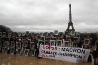 FILE - In this Dec. 8, 2019 file photo, a hundred activists hold portraits of President Emmanuel Macron to urge France to take action during the U.N. COP 25 climate talks in Madrid, during a gathering at Place du Trocadero facing the Eiffel Tower in Paris, France. World leaders breathed an audible sigh of relief that the United States under President Joe Biden is rejoining the global effort to curb climate change, a cause that his predecessor had shunned. (AP Photo/Francois Mori, File)